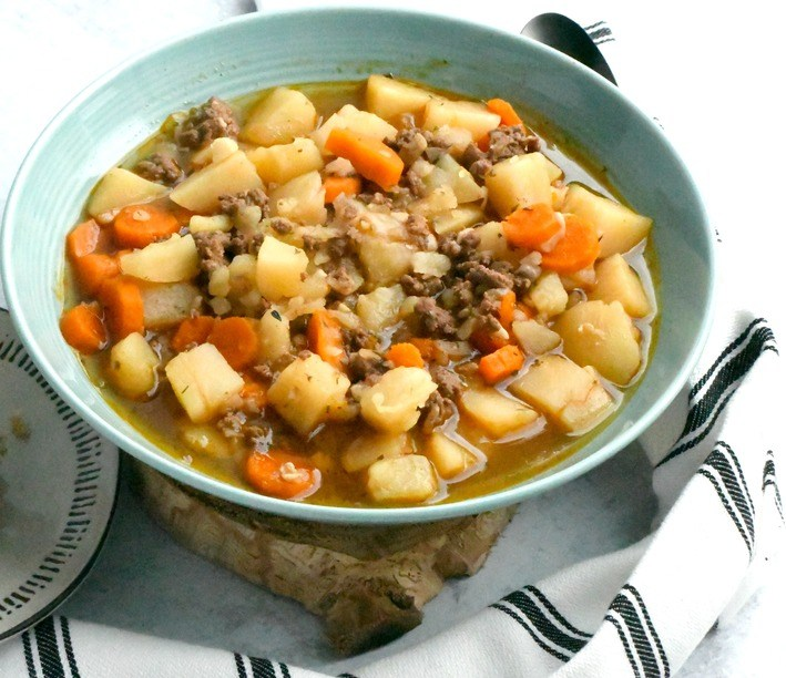 Paleo hamburger soup in a bowl with a towel