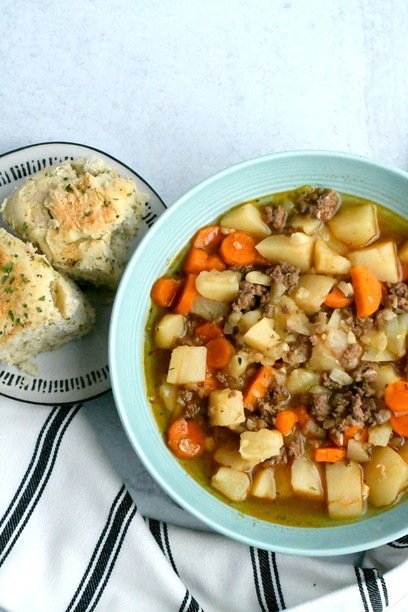 healthy hamburger soup in a bowl with bread on a plate
