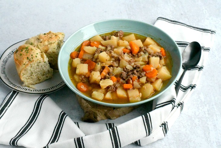 instant pot hamburger soup in a bowl with a towel, bread and spoon