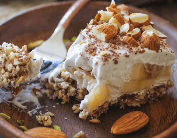 no bake vegan coconut cream pie on a plate with a bite