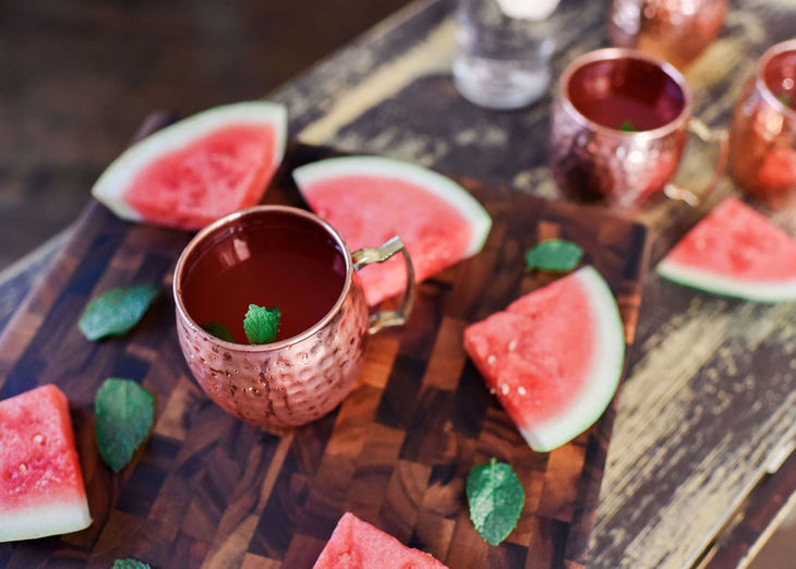 watermelon moscow mule on a table with slices of watermelon