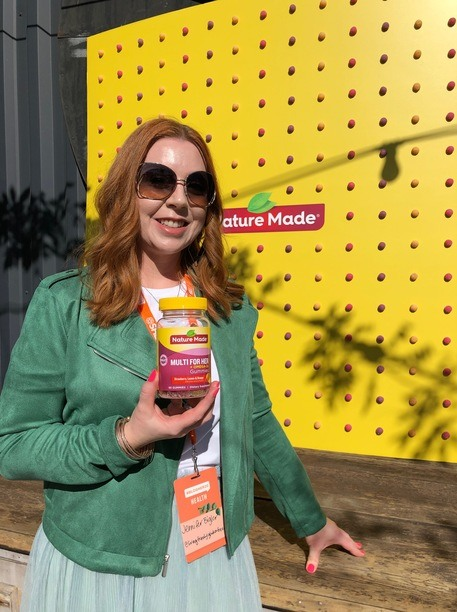 Jennifer Bigler standing with a bottle of Nature Made vitamins