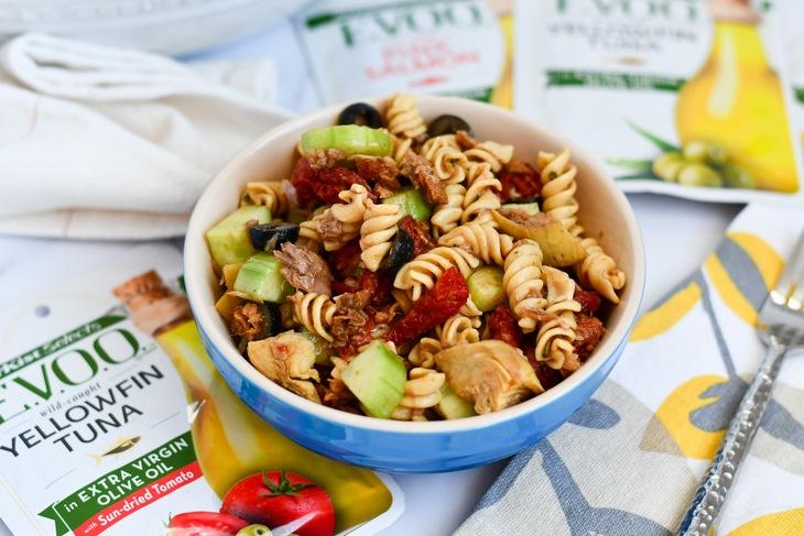 pasta salad in a bowl on a table with pouches of tuna