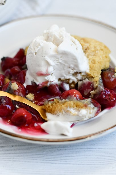 A plate of cherry cobbler with vanilla ice cream on top and a bite on a spoon