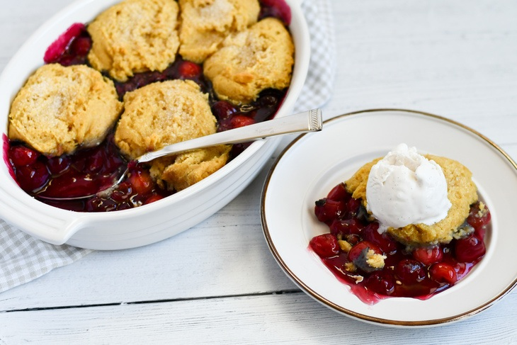 cherry cobbler in a baking dish on a table with a plate of cobbler next to the dish