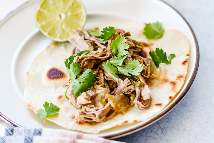 a plate with a tortilla and carnitas on top garnished with lime and cilantro