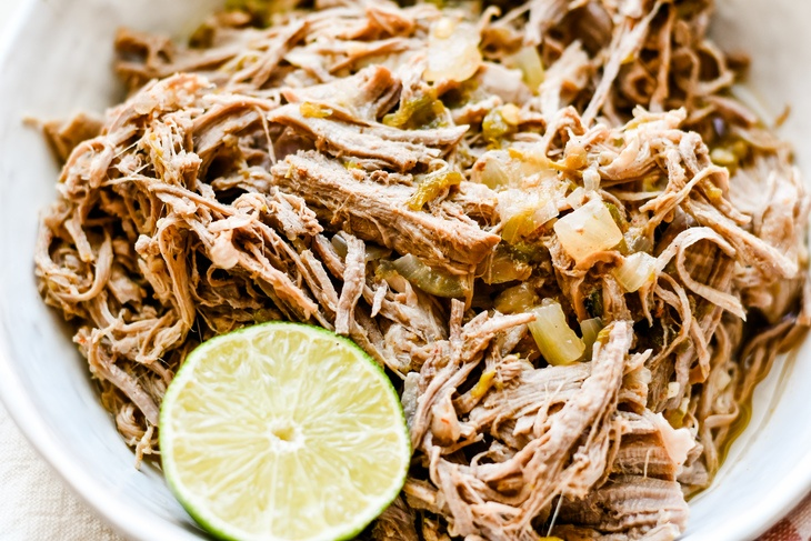 pork carnitas in a bowl garnished with lime