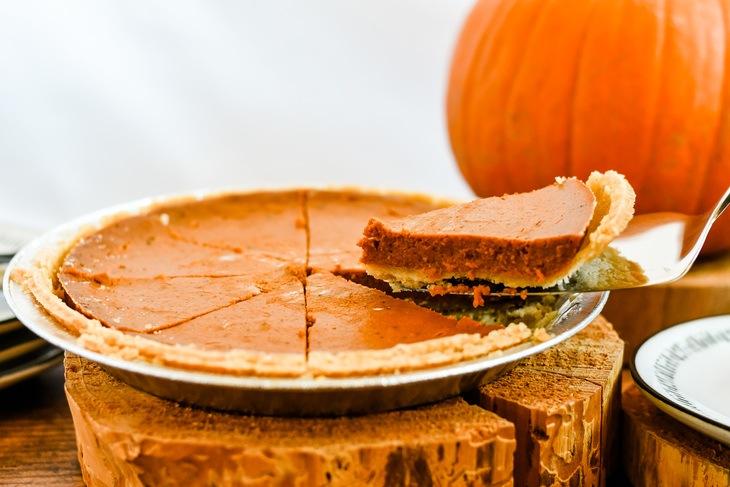 raised gluten free pumpkin pie with a slice being removed