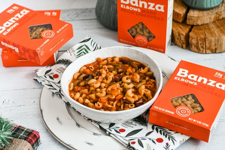 Minestrone soup surrounded by boxes of Banza pasta