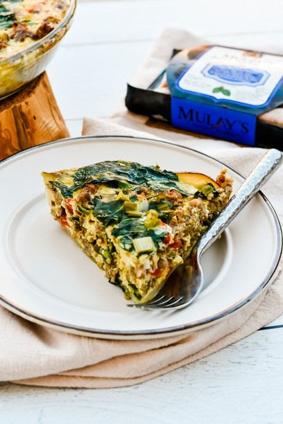 a slice of quiche on a plate with a fork