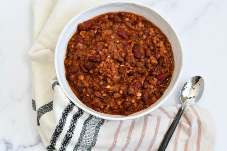 vegan chili in a bowl on the counter with a towel and spoon