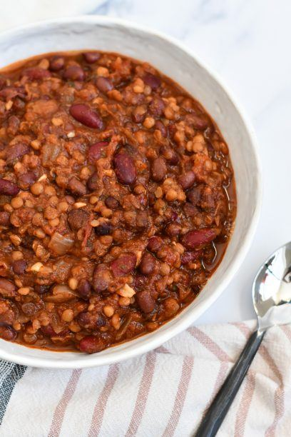vegan chili in a bowl on a table with a towel and spoon