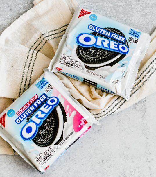 2 packages of gluten free oreo cookies on a table with a kitchen towel