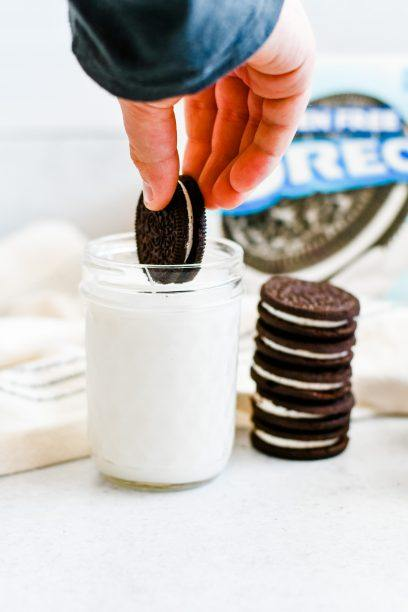 gluten free oreo cookie dipping into a cup of milk