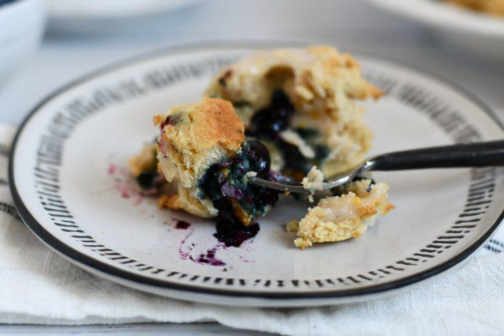 gluten free lemon blueberry scone on a plate with a bite taken out on a fork
