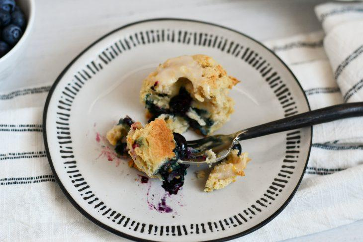 blueberry lemon scones on a plate with a bite on a fork