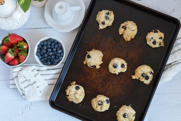 lemon blueberry scones on a sheet pan with a towel