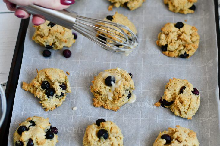 lemon blueberry scones on a sheet pan with icing being drizzled over the top