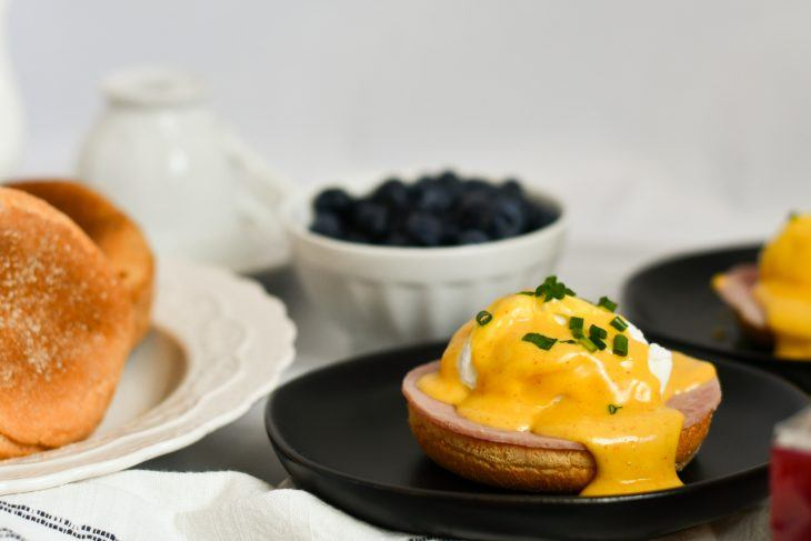 eggs benedict on a plate with english muffins and berries in teh background