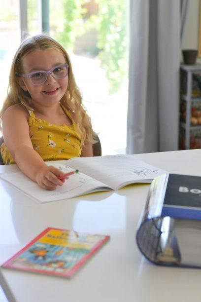 child sitting at the table doing work from the bookshark curriculum