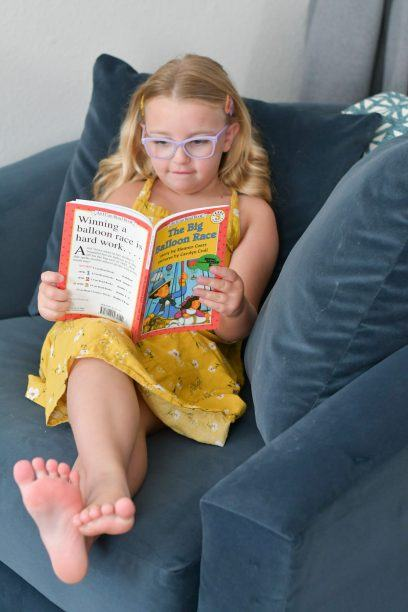 child sitting in a chair reading from the bookshark language arts curriculum