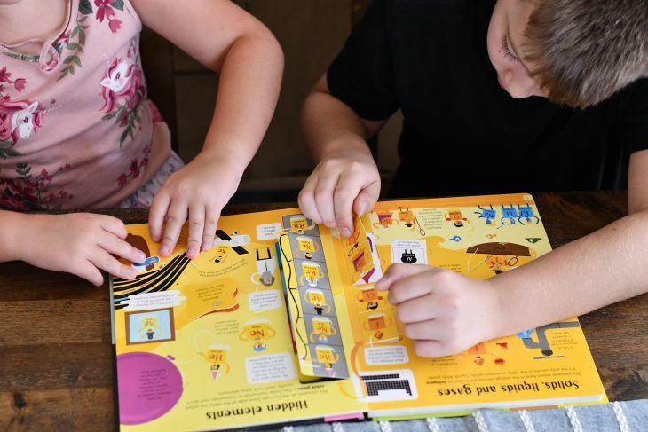 kids flipping through a bookshark science book