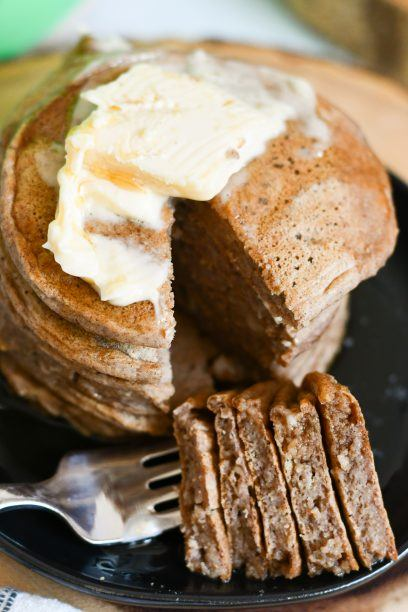 stack of gluten free protein pancakes with a big bite on a fork.