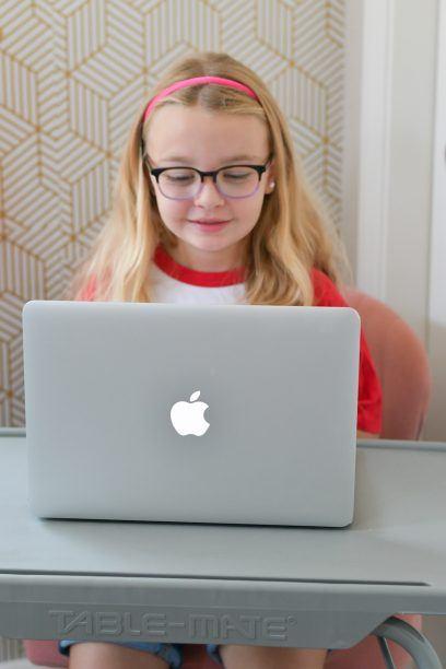 student sitting and working on BookShark virtual curriculum