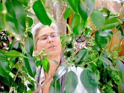 Carmen in her garden with baby hummingbirds
