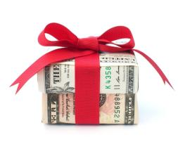 a box made of money with a red bow ties around it. Get a gift for your downpayment for a house