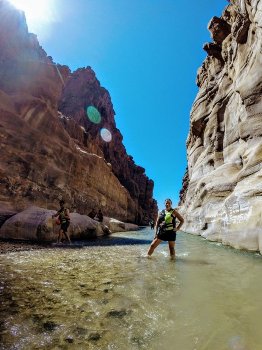 Hiker standning in knee high water at Wadi Mujib Canyon Jordan