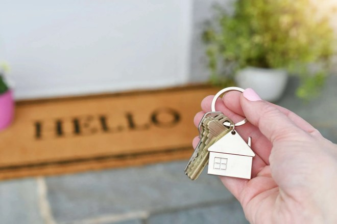 Holding the keys to a new house on the front porch with a HELLO welcome mat.