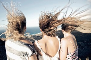 Hair of three women blown by strong wind at beach