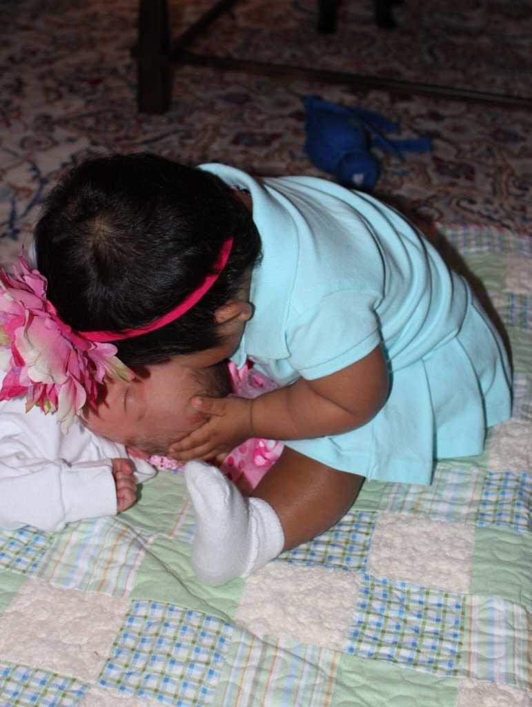 """""""Little Bit"""" kissing newborn baby Brielle. """"Little Bit"""" was 8 months old when Brielle was born."""