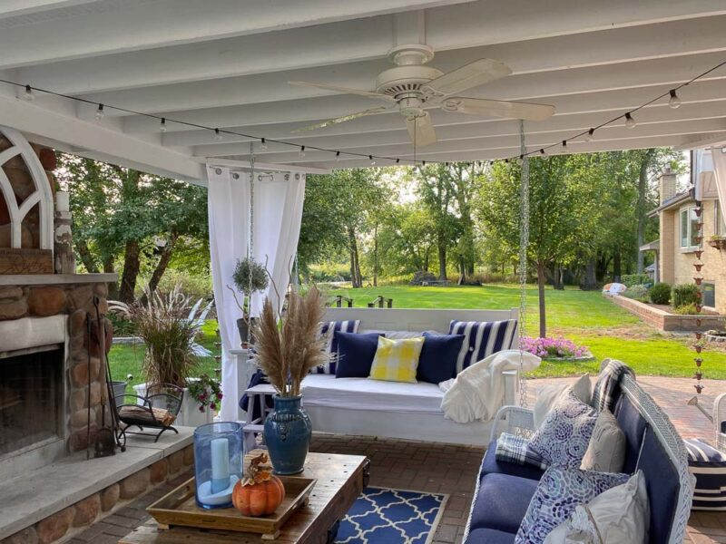 Outdoor Living Room with a white wooden swing bed, white wicker couch, train cart coffee table