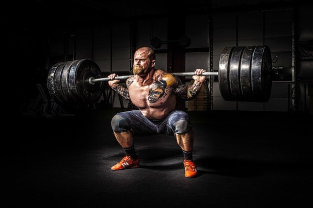 man strength training squat