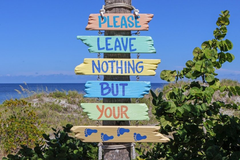 Please Leave Nothing But Your Footprints sign by beach
