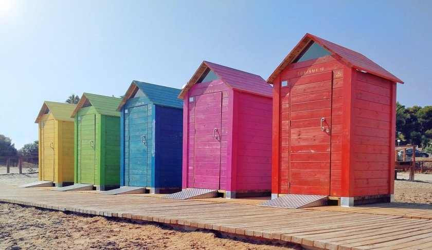 A row of colourful beach huts.
