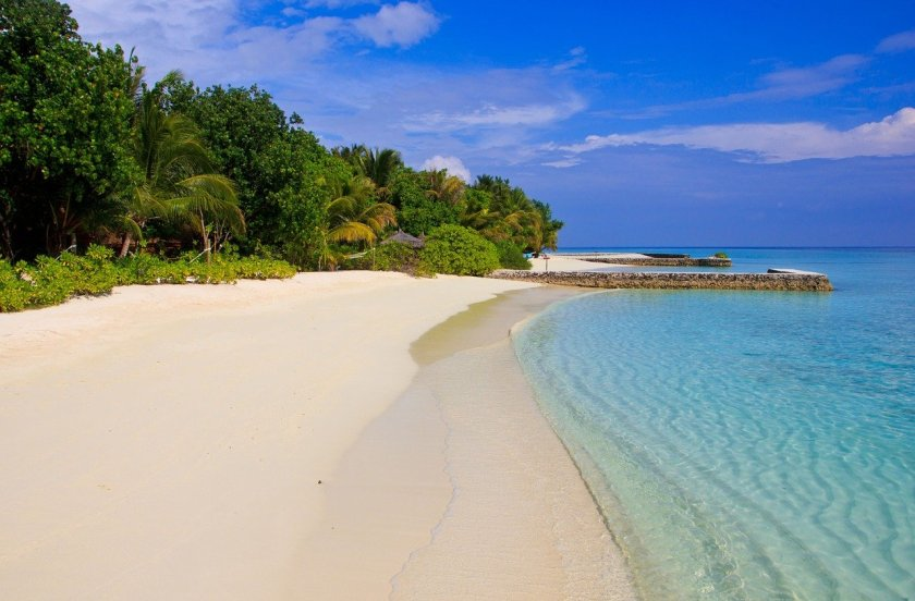 A picture of a beautiful empty sandy beach with gorgeous clear blue ocean.