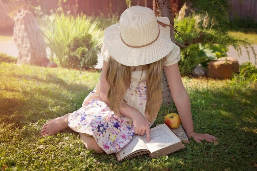 Child sat outside on the grass in sunshine reading a book.