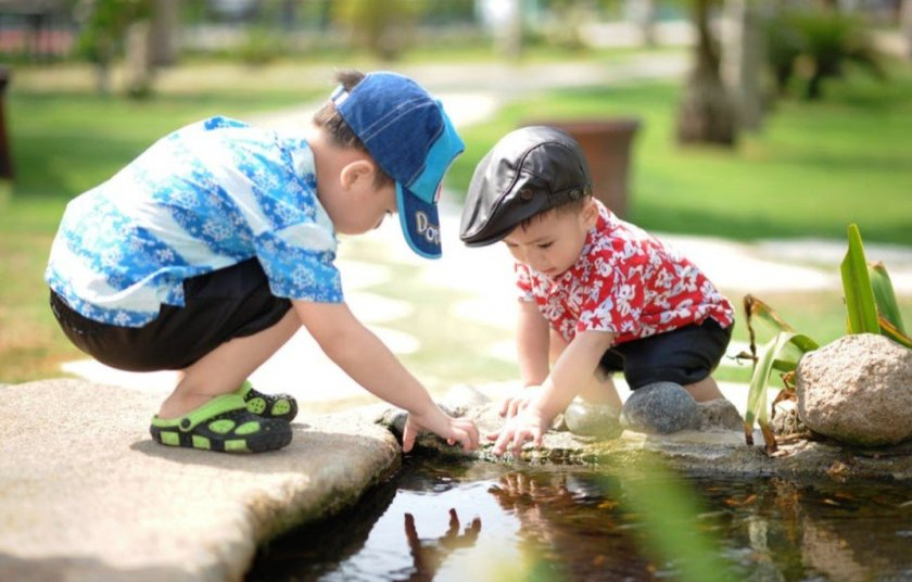 Two children outdoors studying something on the ground next to a pond.