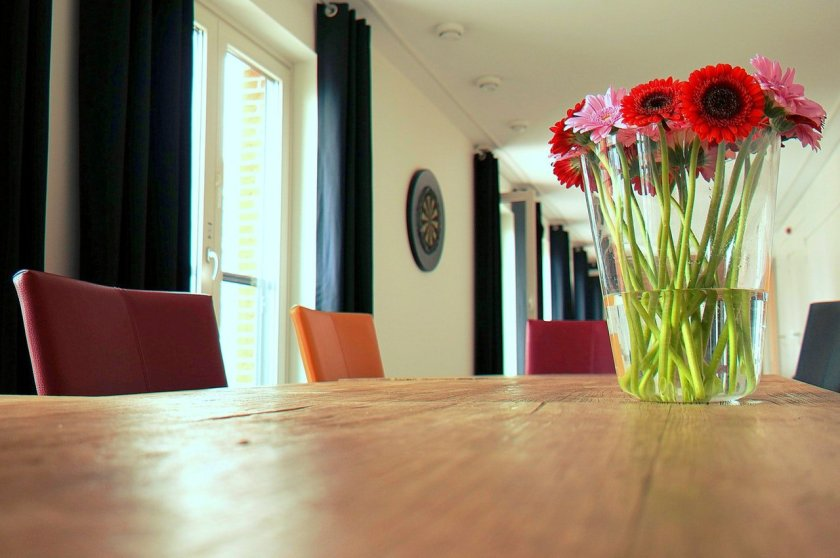 A vase of flowers on a wooden table in a large bright room.