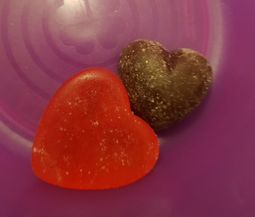 Two hearts - one sweet and one chocolate - in a bowl.