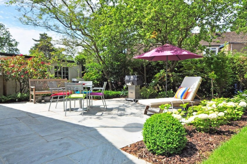 An image of a garden patio with various items of furniture, including sun lounger, table and chairs, and a bench. Plus parasol for shade.