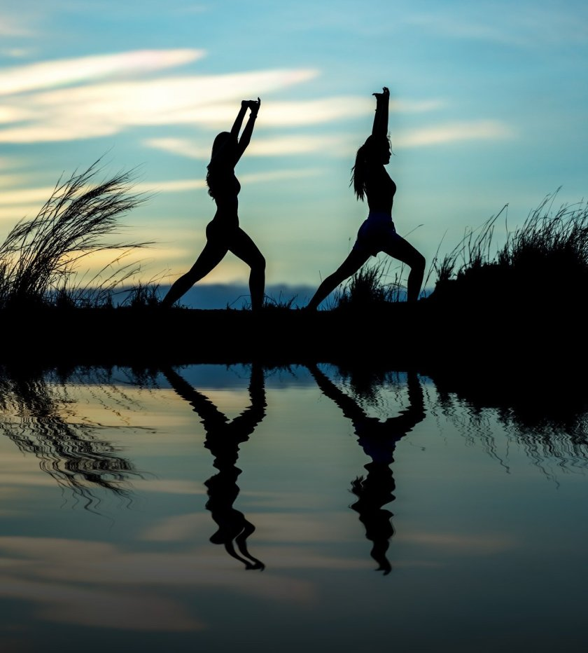 Silhouette of two women doing yoga outdoors