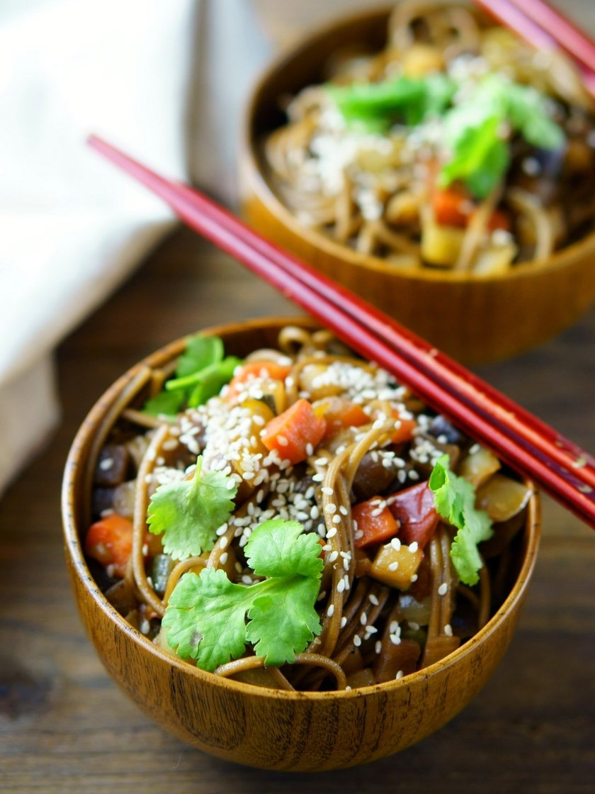 Delicious noodle dish in a wooden bowl with chopsticks