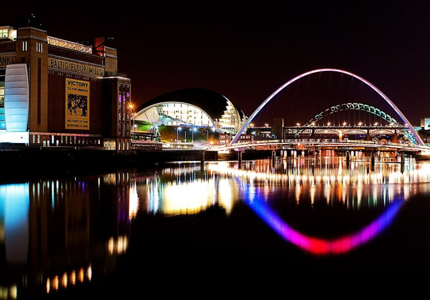 A photo of Newcastle at night. Colourful lights illuminate the river Tyne