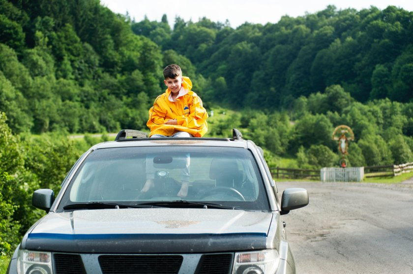 Boy sitting on top of car, through sun roof.