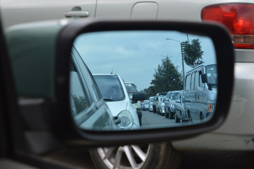 Queue of traffic in rear view car mirror