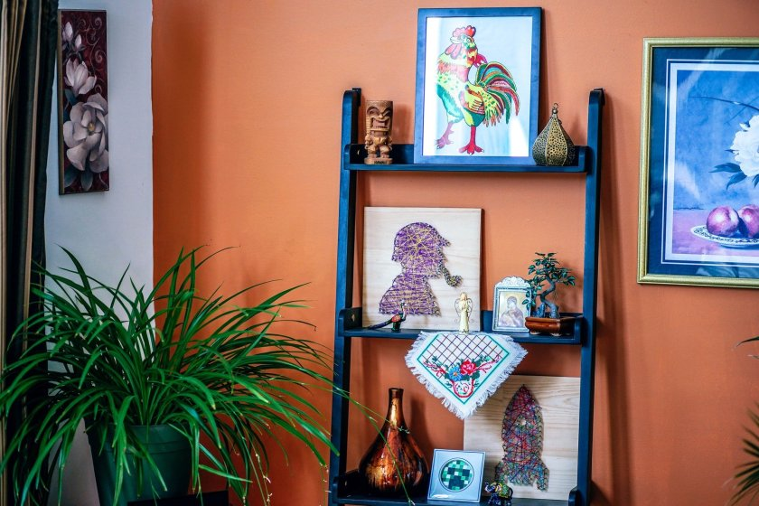 A shelf full of artwork with a green plant in the corner of the room